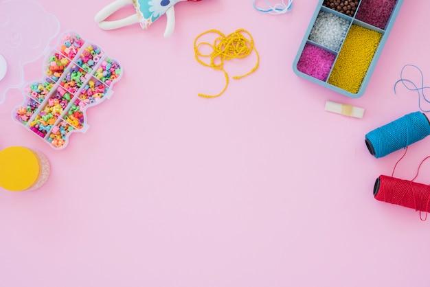 Cuentas de colores caja y carretes de hilo sobre fondo rosa