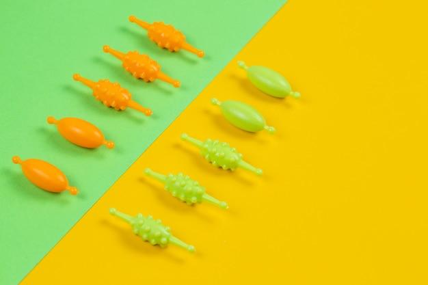 Cuentas de plástico multicolores para una pulsera de niña de un juego de costura sobre un fondo de color con un lugar para el texto