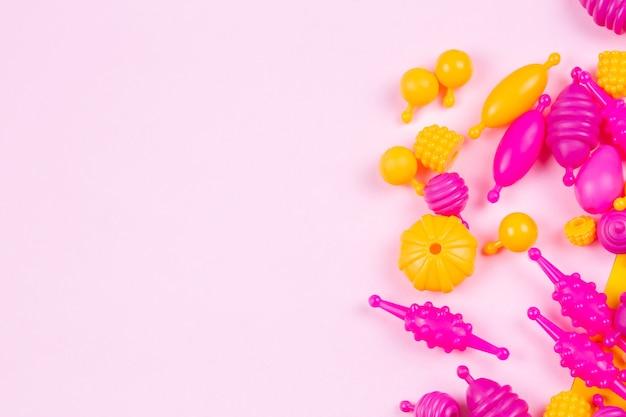 Cuentas de plástico multicolores para una pulsera de niña de un juego de costura sobre fondo rosa con un lugar para el texto