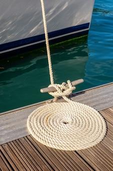 Cuerda de amarre organizar en círculo en el muelle de madera con agua azul