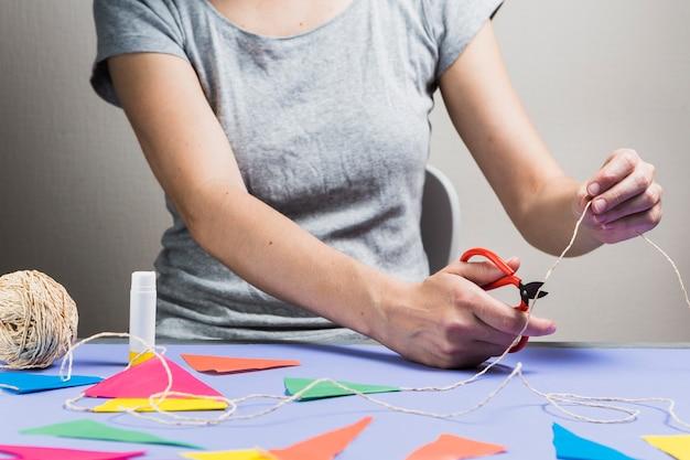 Cuerda de corte de mano de mujer con tijera durante la fabricación de empavesado