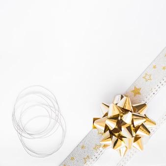 Cuerda de plata y lazo de cinta sobre fondo blanco