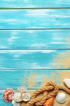 Cuerda de mar con muchas conchas de mar diferentes en el arena de mar sobre un fondo de madera azul. vista superior