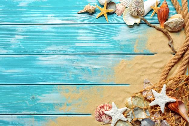 Cuerda del mar con muchas conchas marinas diferentes en la arena de mar sobre un fondo de madera azul en la vista superior