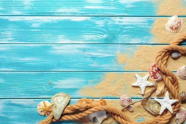Cuerda del mar con muchas conchas marinas diferentes en la arena de mar en una vista superior de madera azul