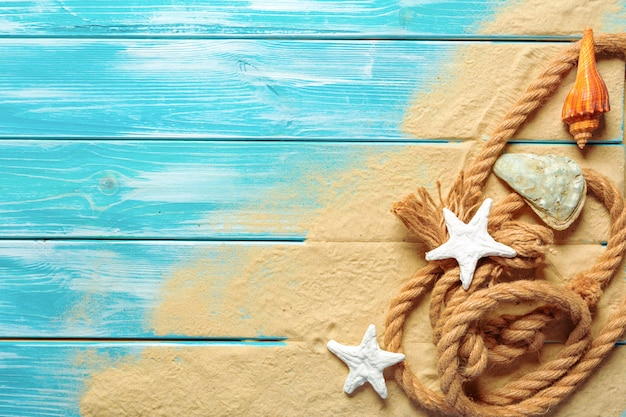 Cuerda del mar con muchas diversas cáscaras del mar en el arena de mar en un fondo de madera azul. vista superior