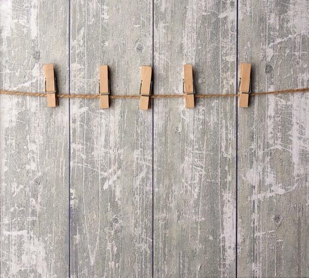 Cuerda marrón y pinzas de madera, fondo para el diseñador