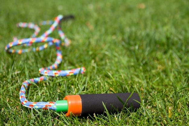 Cuerda que salta en fondo de la hierba verde. entrenamiento físico al aire libre con cuerda de saltar.