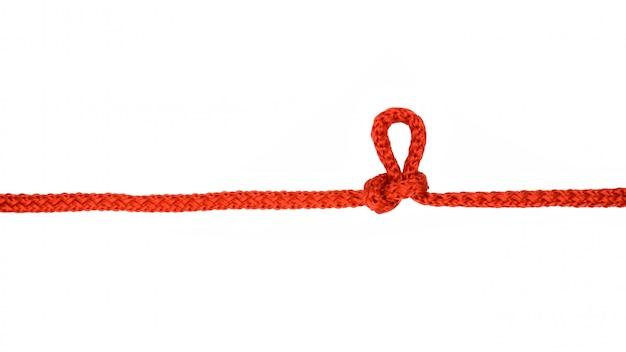 Cuerda roja con nudo aislado sobre fondo blanco.