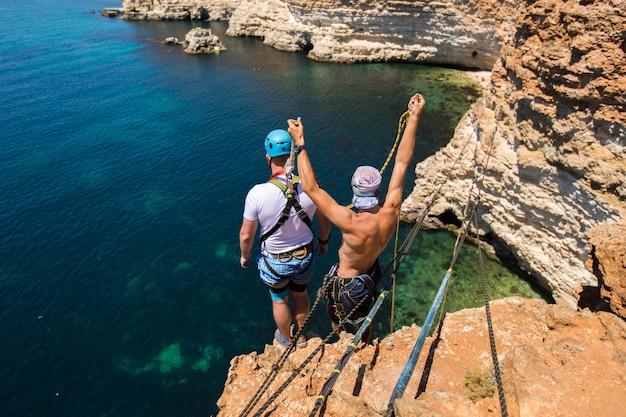 Cuerda saltando de un acantilado con una cuerda en el agua