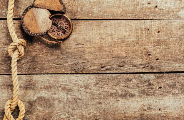 Cuerdas de barco y brújula sobre fondo de madera