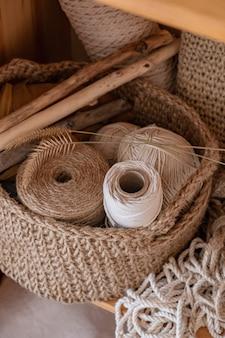 Cuerdas de macramé, algodón y cáñamo en madejas. ganchillo, redes de objetos de artesanía en una canasta de yute