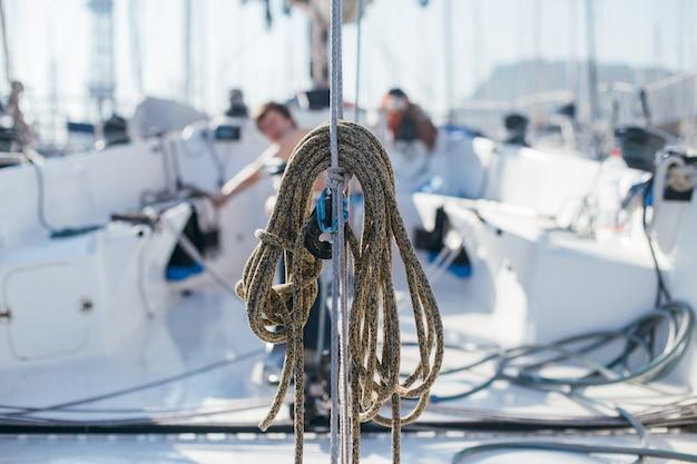 Cuerdas náuticas, buntine, cabrestante y cablet amontonadas en la cubierta de un yate o velero de competición profesional, unidas al mástil o estay de proa, diferentes colores
