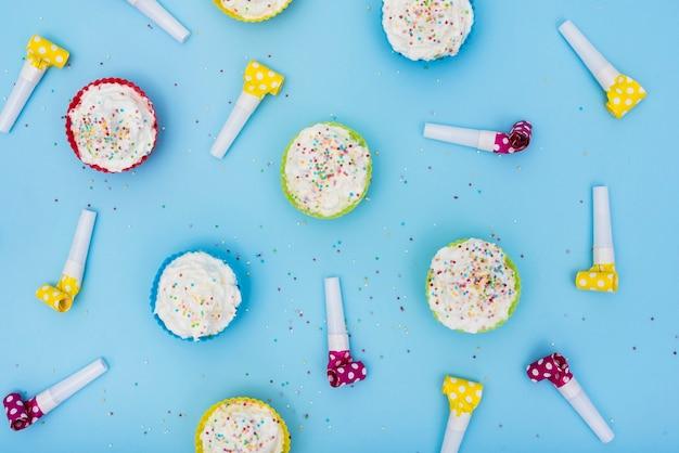 Cuernos de fiesta multicolores y cupcakes.