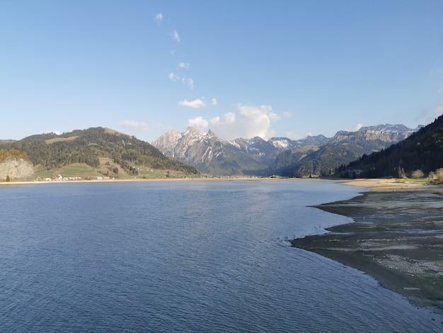 Cuerpo de agua cerca de la montaña bajo el cielo azul durante el día