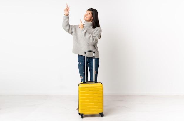 Un cuerpo completo de una mujer viajera con una maleta sobre una pared blanca que señala con el dedo índice una gran idea