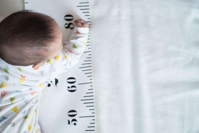 Cuerpo de bebé y cinta métrica: concepto de crecimiento del bebé, altura, desarrollo