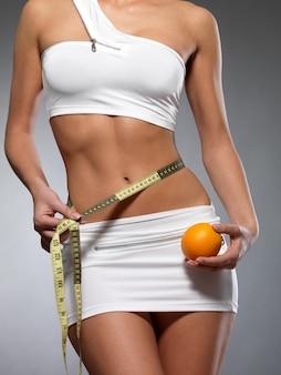 Cuerpo femenino de belleza con cinta métrica y naranja. cocnept de estilo de vida saludable.