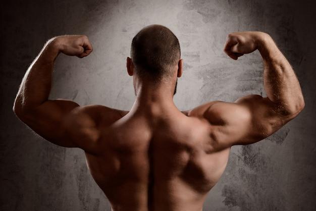 El cuerpo del hombre deportivo sobre la pared oscura.