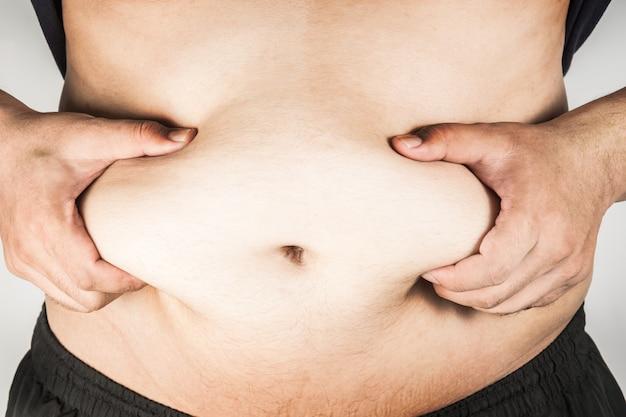 Cuerpo de hombre con sobrepeso con las manos tocando la grasa del vientre.