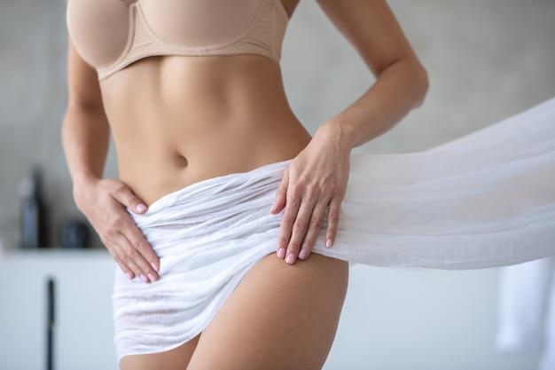 Cuerpo de mujer envuelto con una toalla blanca después de una ducha