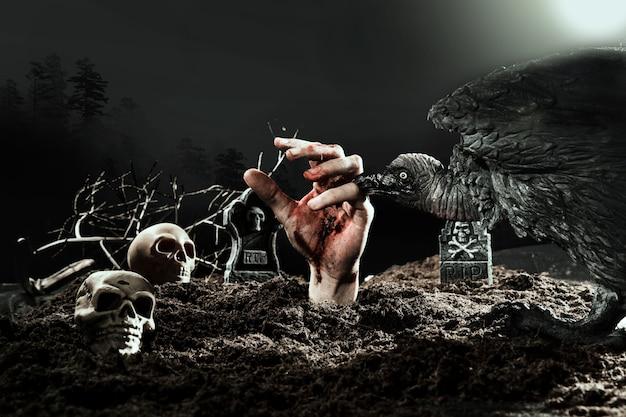 Cuervo espeluznante mordiendo la mano de zombie en el cementerio de halloween