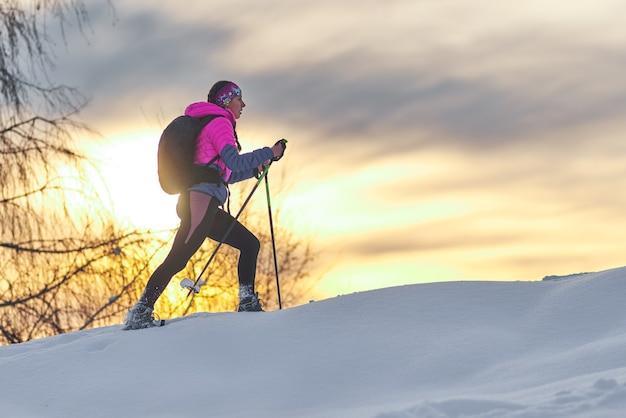 Cuesta arriba con raquetas de nieve. una mujer joven sola