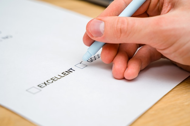 Un cuestionario con opciones de respuesta para el formulario de comentarios. un hombre marca una casilla en un papel blanco