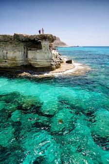 Cuevas marinas de cavo greco cabo. ayia napa, chipre con hombres