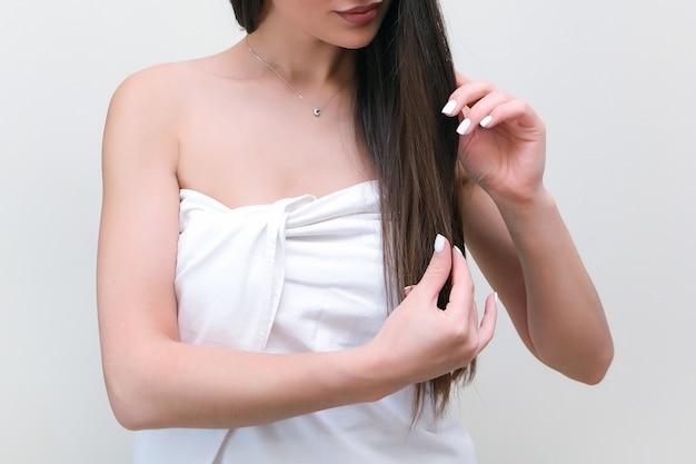 Cuidado del cabello. hermosa mujer joven en una toalla toca su cabello con las manos.
