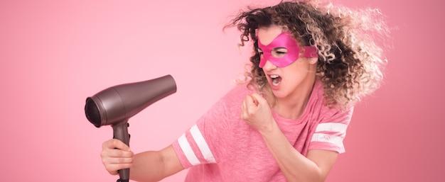 Cuidado del cabello, linda mujer con secador de pelo en la mano