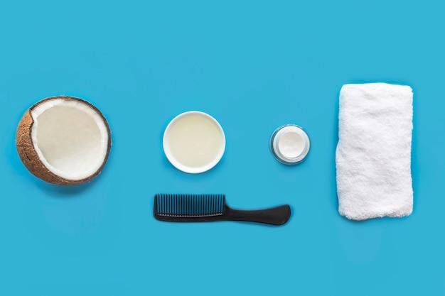 Cuidado del cabello. productos cosméticos de coco: aceite de coco, crema, peine y toalla. conjunto, composición, naturaleza muerta. cosmética orgánica natural. belleza, salud del cabello facial. vista plana lay.top