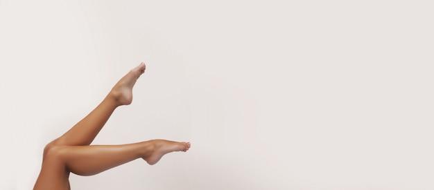 Cuidado del cuerpo de la mujer. cerca de largas piernas bronceadas femeninas con piel suave suave perfecta, pedicura, uñas sanas aisladas. concepto de depilación, belleza y salud. espacio libre para texto pancarta panorámica