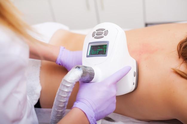 Cuidado del cuerpo. la mujer está en proceso en la clínica de lipomasaje