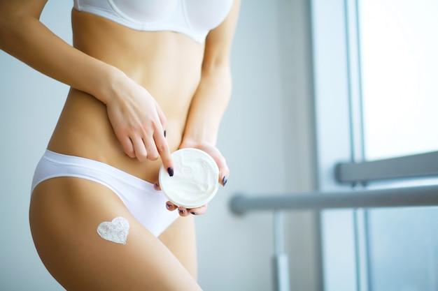 Cuidado del cuerpo. mujer que aplica la crema hidratante en las piernas.