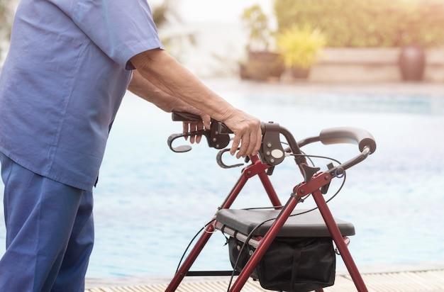 Cuidado y curación médica, paciente anciano maneja de walker andador con asiento y ruedas.