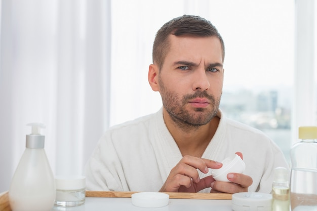 Cuidado facial. agradable hombre agradable sosteniendo una crema facial mientras se preocupa por su piel