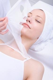 Cuidado facial de la hermosa joven en el salón de spa