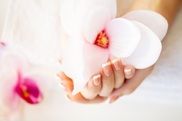 Cuidado de las uñas. hermosas uñas de mujer con manicura francesa, en estudio de belleza