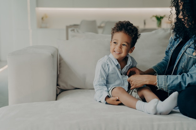 Cuidado mamá afroamericana vistiendo a su pequeño hijo mientras está sentado en el sofá en la sala de estar