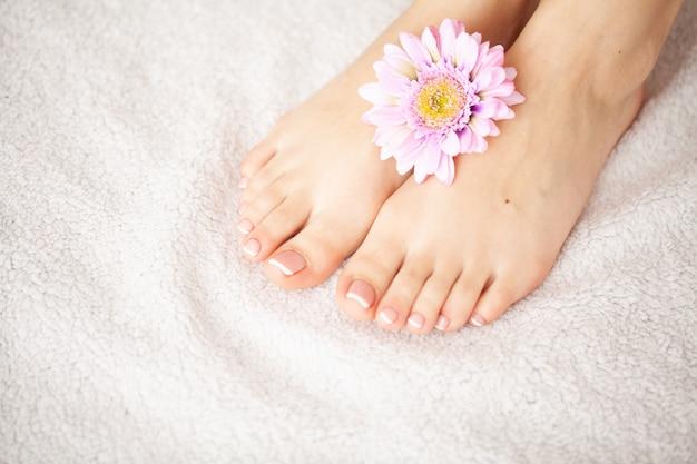 Cuidado de manos y uñas. hermosos pies y manos de mujeres después de la manicura y pedicura en el salón de belleza. manicura spa