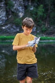 Cuidado de la pantalla del teléfono móvil, el niño lava un teléfono inteligente con agua y espuma del río. el niño inundó el teléfono con agua y lo desactivó.