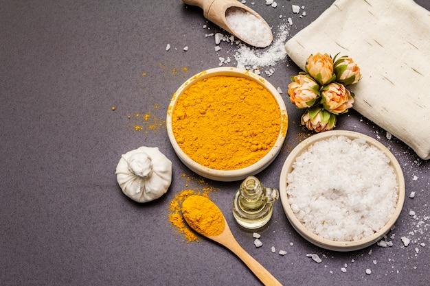 Cuidado personal con ingredientes naturales. concepto de spa saludable. cúrcuma, sal marina, aceite, toalla.