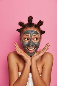 Cuidado de la piel, cosmetología y concepto de bienestar. el modelo positivo de piel oscura extiende las palmas de las manos sobre la cara, aplica una mascarilla hidratante para limpiar la piel, se somete a procedimientos de belleza después del baño, usa una toalla sobre el cuerpo