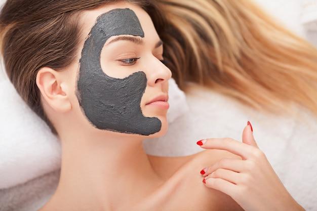 Cuidado de la piel facial. mujer hermosa que consigue la máscara cosmética en salón