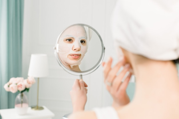 Cuidado de la piel facial y tratamientos de belleza. mujer con una sábana máscara hidratante en la cara y una toalla blanca en la cabeza, mirando al espejo.
