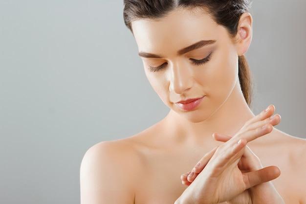 Cuidado de la piel de las manos. cerca de manos femeninas aplicar crema, loción. manos de mujer hermosa con manicura roja.