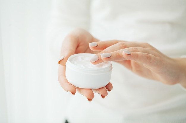 Cuidado de la piel de las manos. cerca de las manos femeninas sosteniendo el tubo de crema, manos de mujer hermosa con uñas de manicura natural aplicando crema de manos cosmética sobre una piel suave, sedosa y saludable.