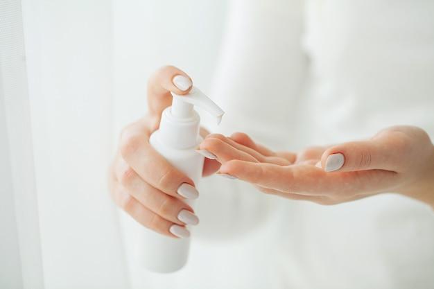 Cuidado de la piel de las manos. cerca de manos femeninas con tubo de crema, manos de mujer hermosa con uñas de manicura natural aplicando crema cosmética para manos sobre piel suave, sedosa y saludable