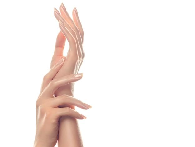 Cuidado de la piel de las manos. manos de mujer hermosa con manicura rosa claro en las uñas.